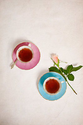 Tea Cups with Rose on Tablecloth - p1248m2125832 by miguel sobreira