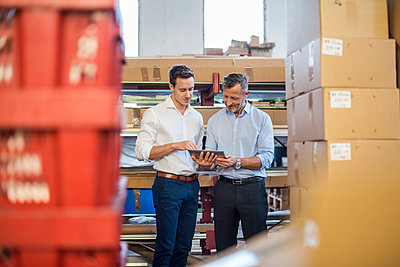 Two businessmen in factory storeroom looking at tablet - p300m1562869 by Daniel Ingold