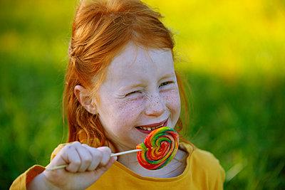 Portrait of happy girl eating a lollipop - p300m2103372 von Anette Christina Götz
