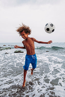 Boy playing with a football on the beach - p300m2132166 by DREAMSTOCK1982
