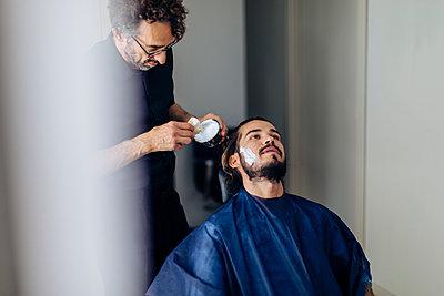 Barber applying shaving cream on client in salon - p300m2203117 by Sofie Delauw