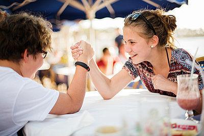 Brother and sister arm wrestling - p312m1180398 by Juliana Wiklund