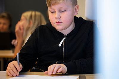 Boy sitting in classroom - p312m2174478 by Scandinav