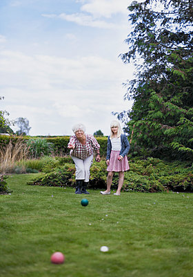 Grandmother and granddaughter playing petanque - p312m2200054 by Pernille Tofte