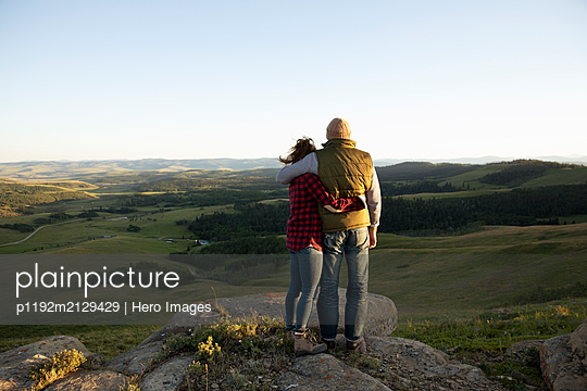 Rear view of young couple standing on rocks - p1192m2129429 by Hero Images