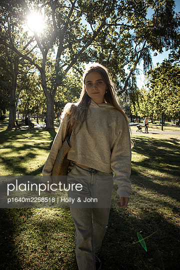 Teenage girl takes a walk in the park - p1640m2258518 by Holly & John