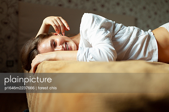 Young woman lying on bed - p1646m2237666 by Slava Chistyakov