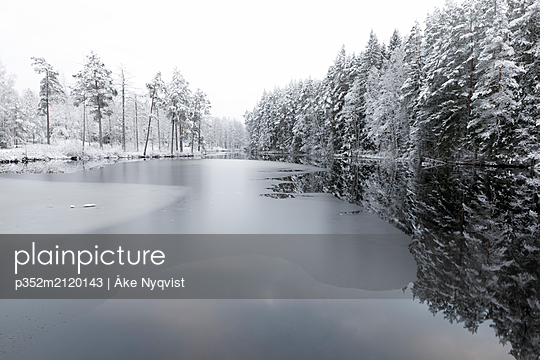 Ice on lake by snow covered trees in Lotorp, Sweden - p352m2120143 by Åke Nyqvist