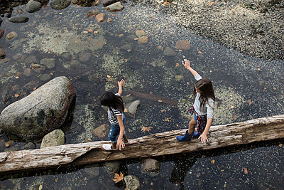 Girl friends walking, balancing on fallen log over water - p1192m1511817 by Hero Images
