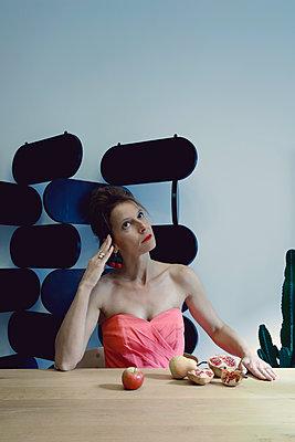 Frau in rosa Kleid sitzt am Tisch mit Früchten - p1521m2133389 von Charlotte Zobel