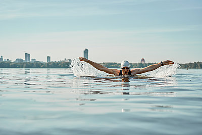 Young swimmer man swimming in style of butterfly on river - p1630m2196910 by Sergey Mironov