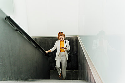 Businesswoman in white pant suit, ascending stairs, using smartphone - p300m2140275 by Eloisa Ramos