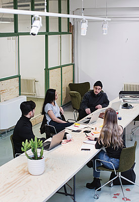 High angle view of four entrepreneurs discussing at desk in creative office - p426m1407193 by Maskot