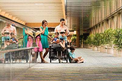 Family waiting in airport using cell phones - p555m1490967 by Mark Edward Atkinson/Tracey Lee