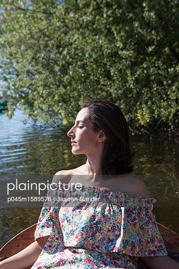 Frau sonnt sich in Ruderboot - p045m1589576 von Jasmin Sander