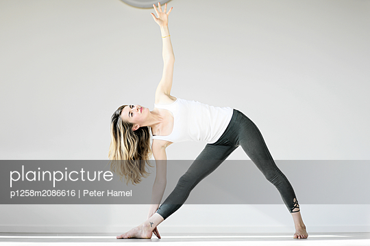 Young woman doing yoga - p1258m2086616 by Peter Hamel
