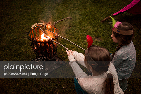 Two girls wearing feather headdress, grilling sausage over camp fire - p300m2005464 von Robijn Page