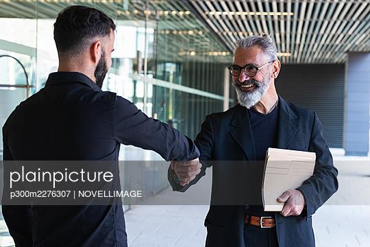 Smiling male entrepreneurs doing handshake at entrance - p300m2276307 by NOVELLIMAGE
