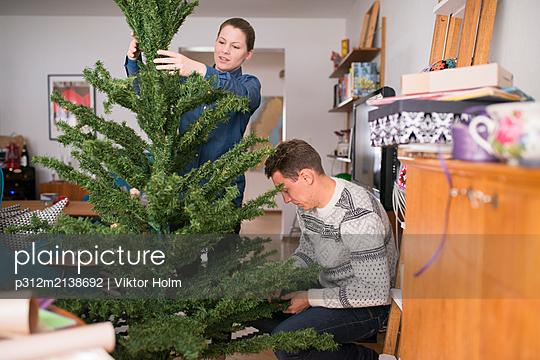 Couple preparing Christmas tree - p312m2138692 by Viktor Holm