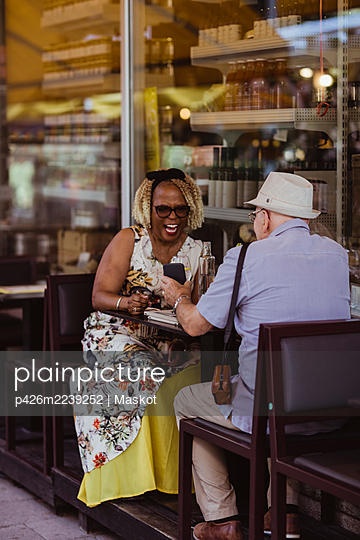 Senior woman laughing while man showing smart phone at sidewalk cafe - p426m2239252 by Maskot