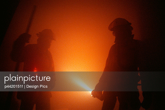 Firemen in smoky room with flashlight