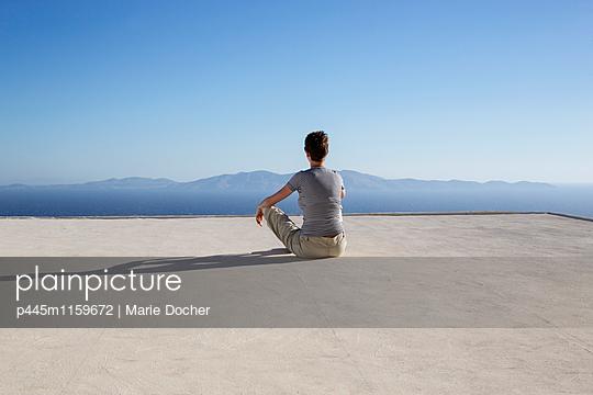 Frau auf einem Hausdach blickt aufs Meer - p445m1159672 von Marie Docher
