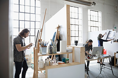Painter painting at canvas on easel near photographers reviewing print in coworking space art studio - p1192m1490170 by Hero Images
