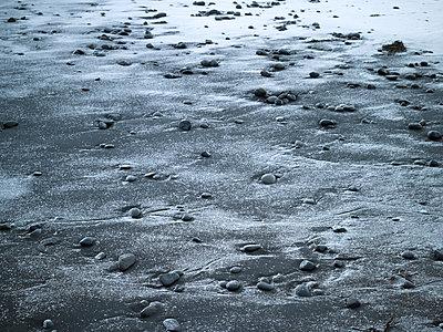 Steine und Schnee auf schwarzem Lavasandstrand - p1314m1189976 von Dominik Reipka