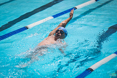 Young Caucasian male swimmer swimming backstroke in swimming pool - p1315m2091028 by Wavebreak