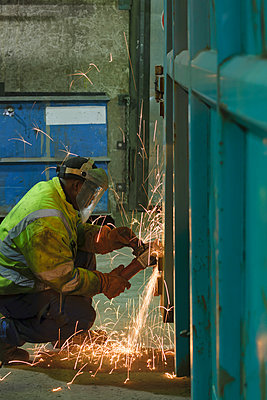 Man working at container in a scrap metal recycling plant - p300m950397f by Albrecht Weißer