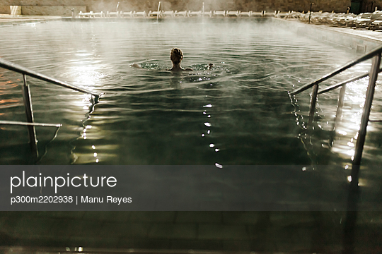 Mid adult woman swimming in hot pool at tourist resort during night - p300m2202938 by Manu Reyes