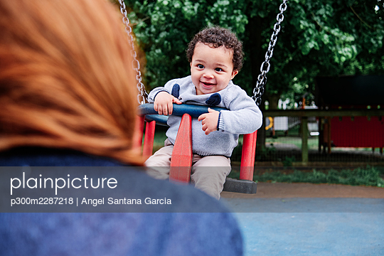 Smiling boy looking at woman while sitting on swing in playground - p300m2287218 by Angel Santana Garcia