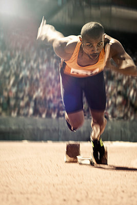 Runner taking off from starting block on track - p1023m946890f by Tom Merton