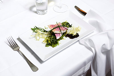 A salad placed on a table at a fine dining establishment, close-up - p1094m900227 by Patrick Strattner