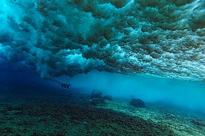 Under water view of wave, surfer sitting on surfboard, underwater shot - p1166m2290291 by Cavan Images