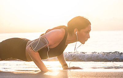 Woman wearing headphones doing push-up on beach - p1427m2124073 by Tetra Images