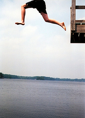 A person jumping off a platform into a lake - p3012846f by fStop