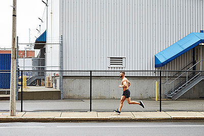 Shirtless man jogging on pavement along fence of industrial building, Boston, Massachusetts, USA - p343m1577977 by Josh Campbell