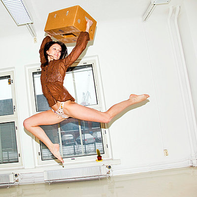 Woman jumping with a box - p4130543 by Tuomas Marttila