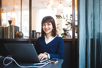 Portrait of smiling female entrepreneur sitting with laptop at office - p426m2089035 by Maskot