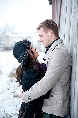 Young couple hugging against cabin in snow - p429m2050835 by Sara Monika