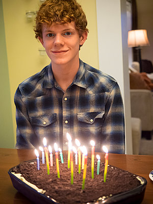 Caucasian boy smiling with birthday cake - p555m1411506 by Jeff Greenough