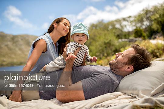 Familie mit Baby entspannt sich am Seeufer - p1355m1574049 von Tomasrodriguez