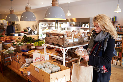 Woman Shopping For Organic Bread In Delicatessen - p1407m1507543 by Monkey_Images