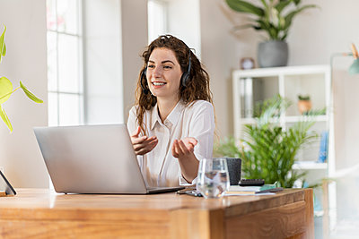 Smiling female woman gesturing while talking through headphones at home office - p300m2276462 by Steve Brookland