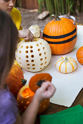 Over shoulder view of girl and brother preparing pumpkins on garden table - p924m1468959 by Kinzie Riehm