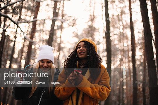 Happy girlfriends walking among trees in park during winter - p1166m2268824 by Cavan Images