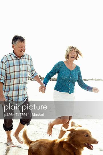 Happy couple running behind dog at beach
