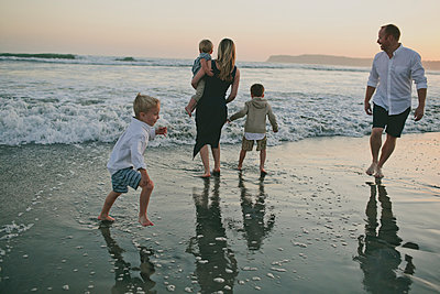 Family enjoying at beach during sunset - p1166m1530870 by Cavan Images