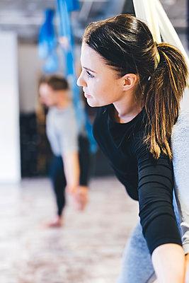 Friends practicing aerial yoga in gym - p1166m1576482 by Cavan Images